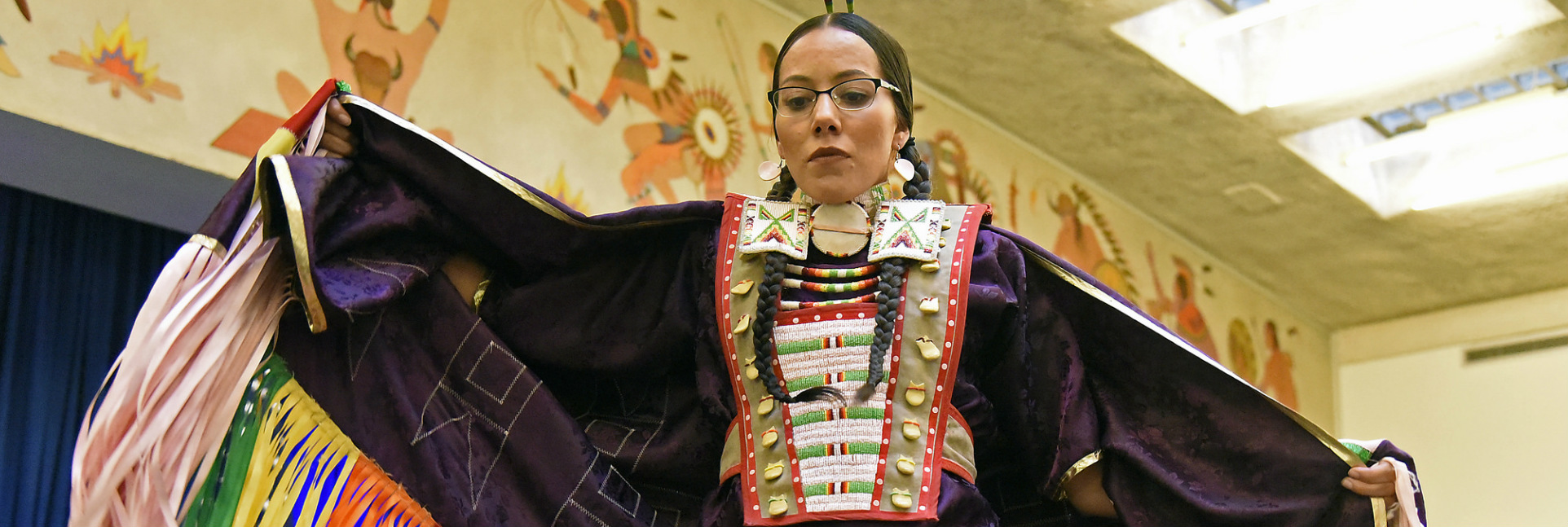 A Native American woman in elaborate traditional clothes dances in front of a Native American mural in a large room.