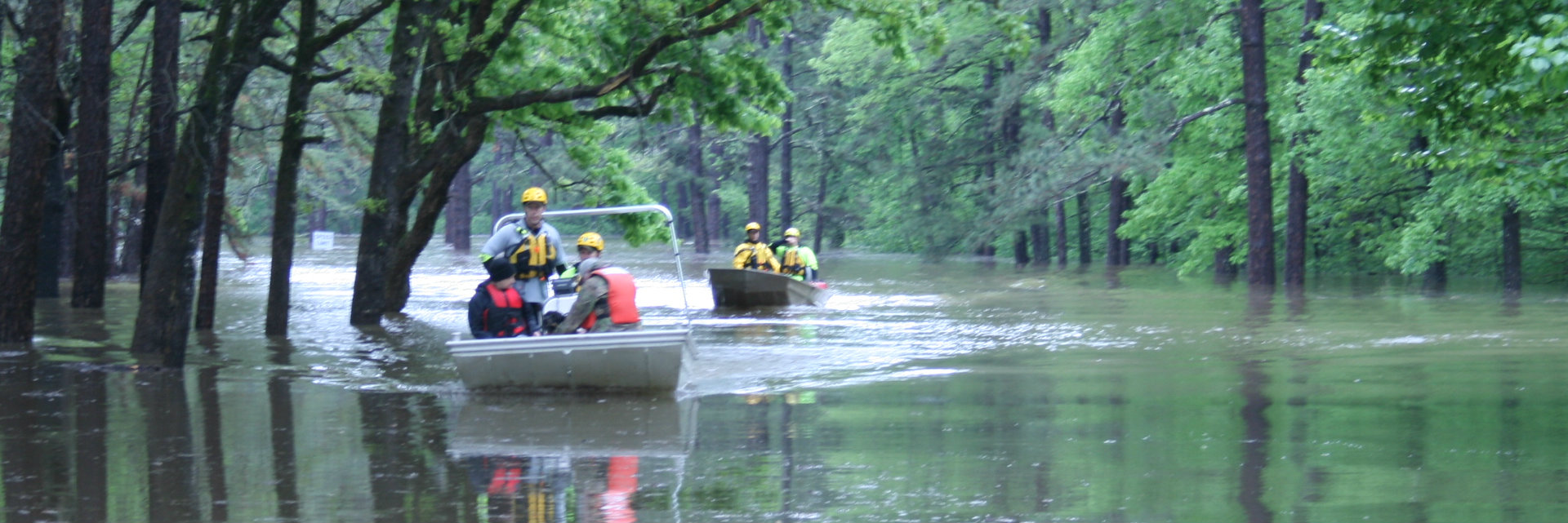 Rangers in boat travel through flooded water next to trees.