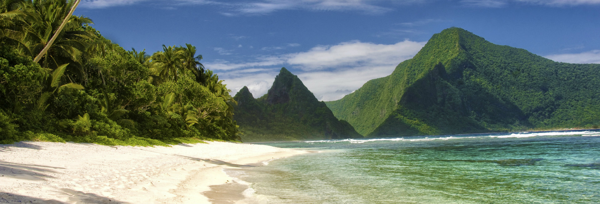 Green Trees And Mountain Loom Over The Sandy Beach At National Park Of  American Samoa.