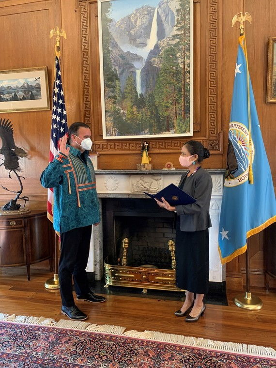Secretary Deb Haaland swears in Bryan Newland in front of two flags and a fireplace.