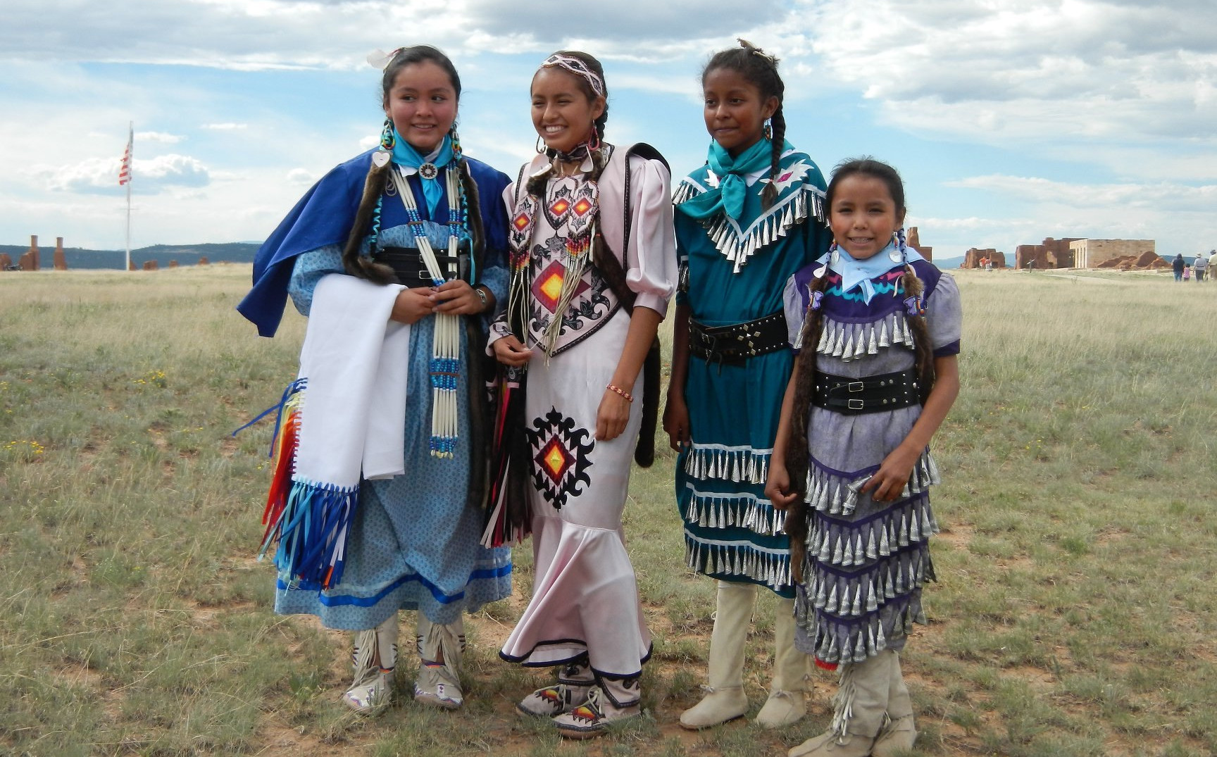 Four young girls in traditional Native American clothes pose together in grassy field.