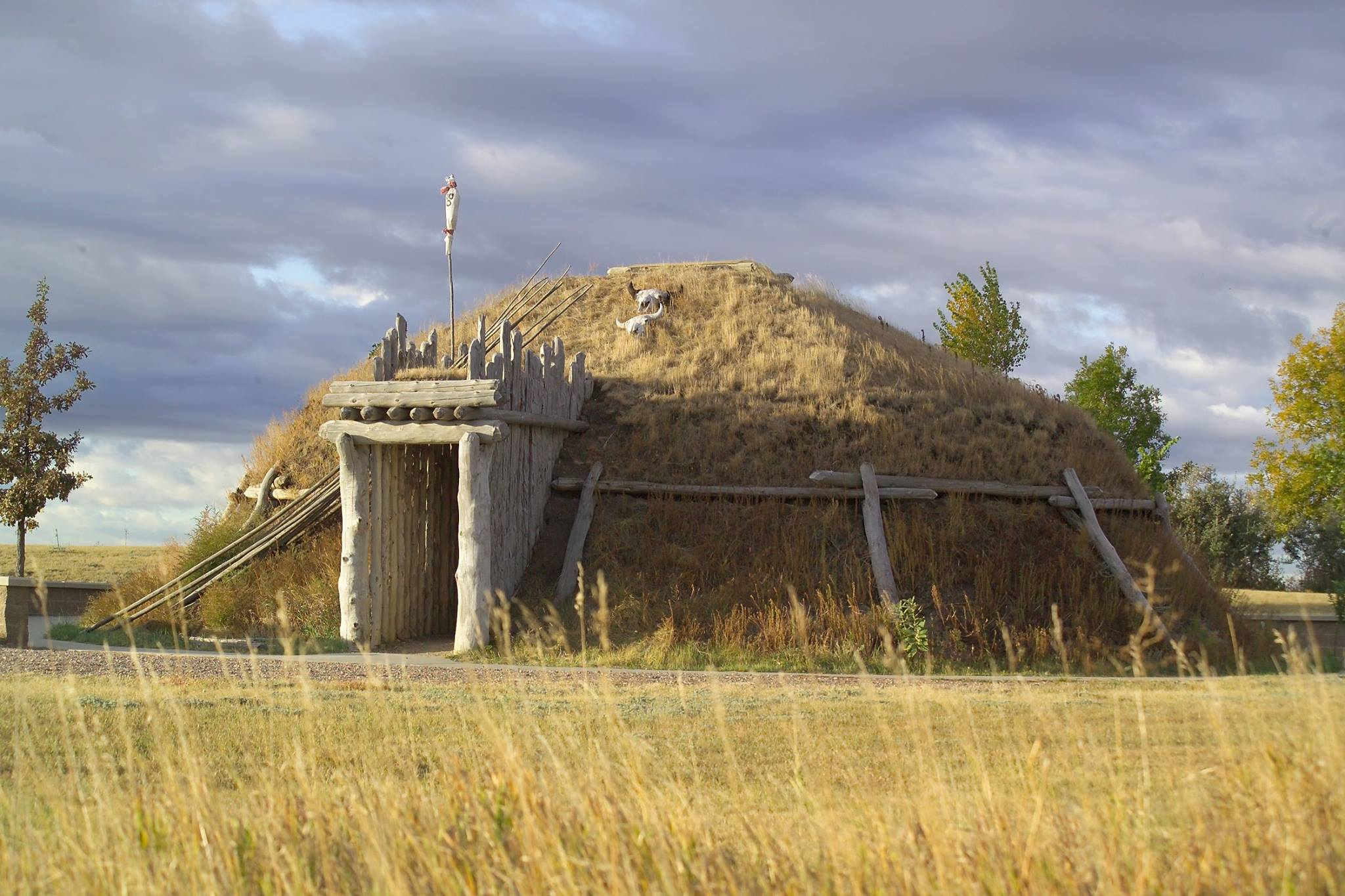 A round lodge covered in grass and dirt with a wooden entry ways.