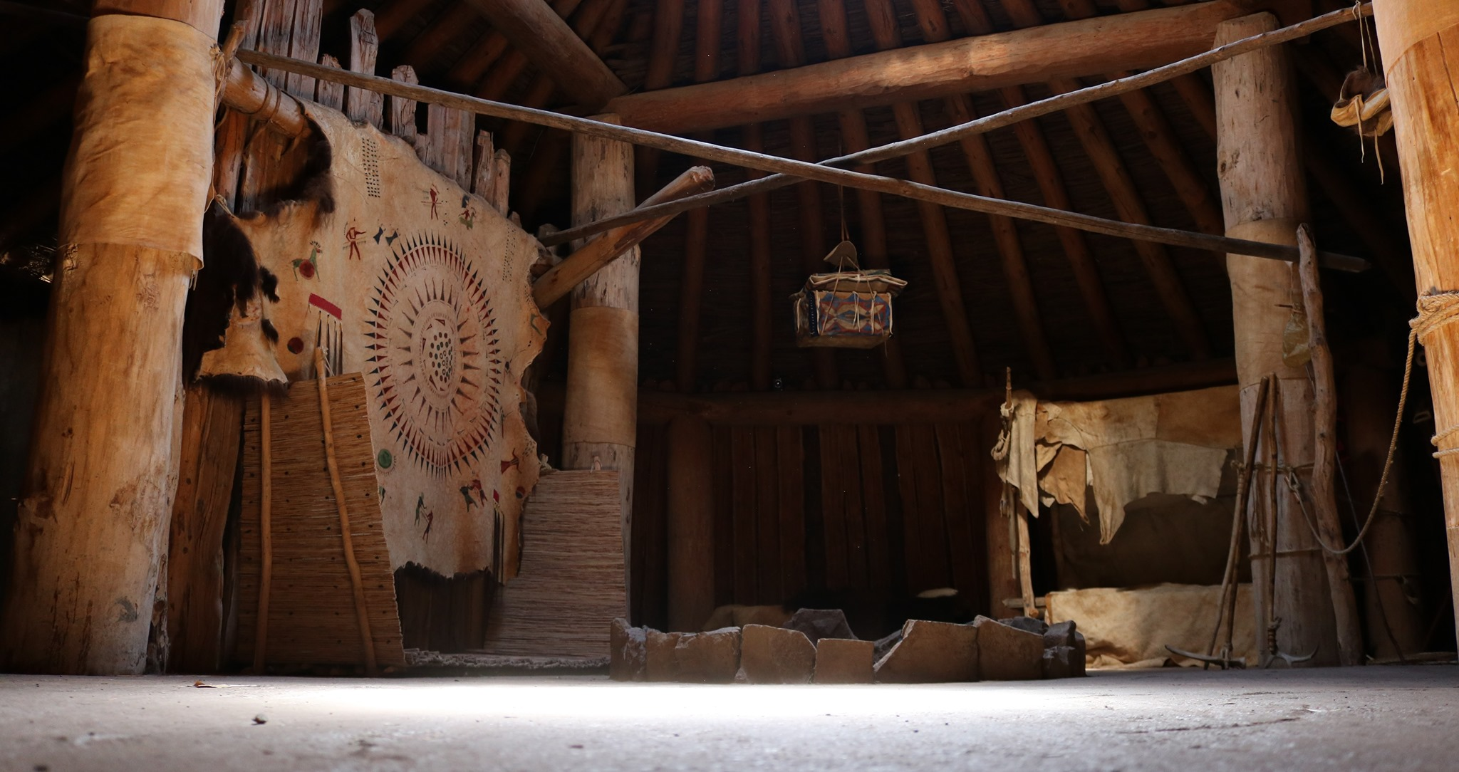 The inside of a wooden lodge is decorated with animal hides and has a fire circle in the middle.