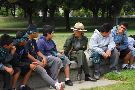 Betty Reid Soskin seated on a stone wall talking to a group of young boys visiting the park.