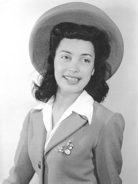 Photo of a 20-year-old Betty wearing a hat and suit.