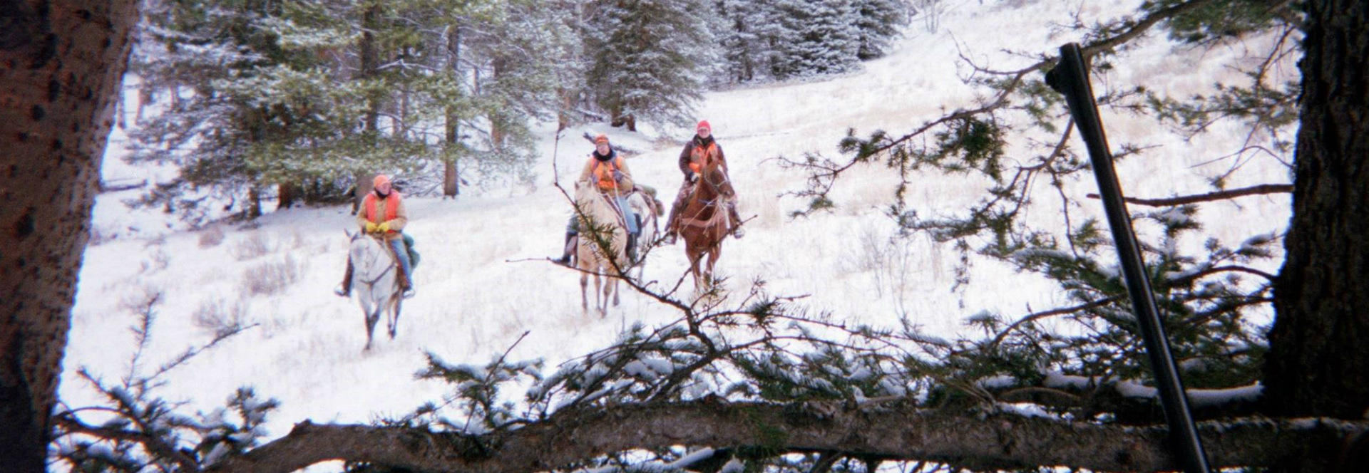 Three people wearing camouflage hunting gear ride horses through a snow covered forest.