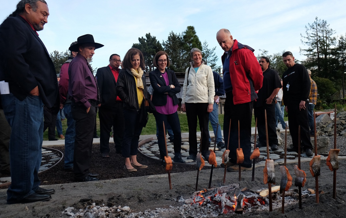Secretary Jewell and other officials with salmon cooking on skewers at a campfire.