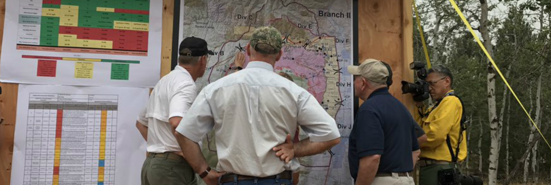 Three men in white men in polo shirts and ballcaps look at a large map pinned to a wooden board in the forest.