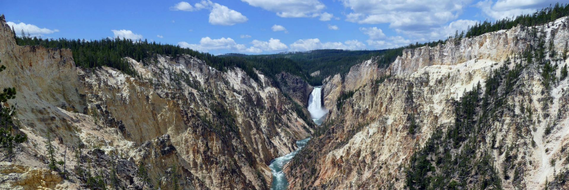 River flows over waterfall in canyon in a bright sunny day