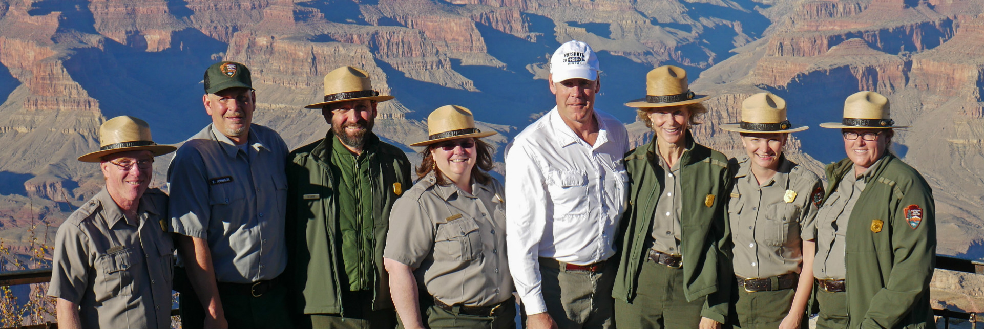 Secretary Zinke poses with a small group of men and women in National Park Service uniforms in front of the Grand Canyon.