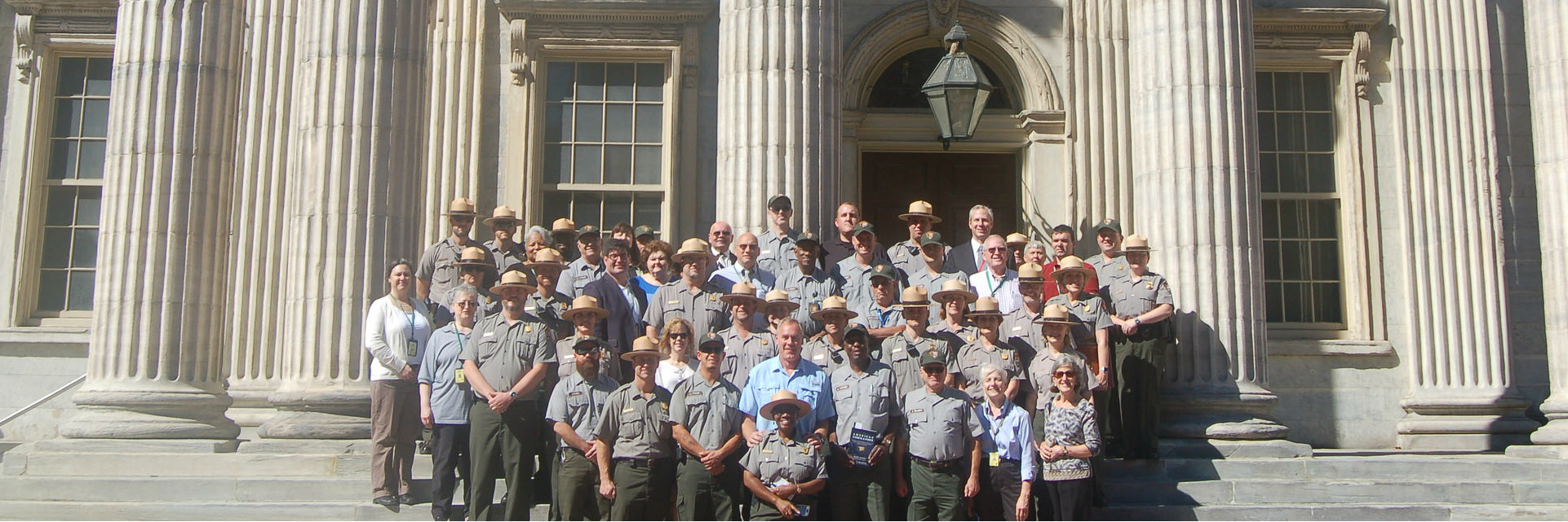 Secretary Zinke poses with a group of about 50 park service employees in uniforms on the steps of an ornate old building.