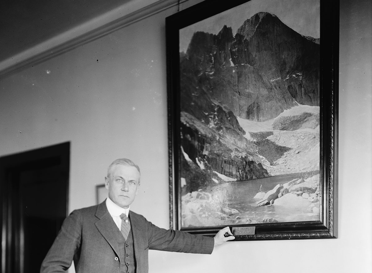 Stephen T. Mather standing by portrait.