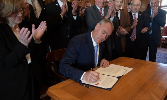 Secretary Zinke signs document as many witness and applaud in the background