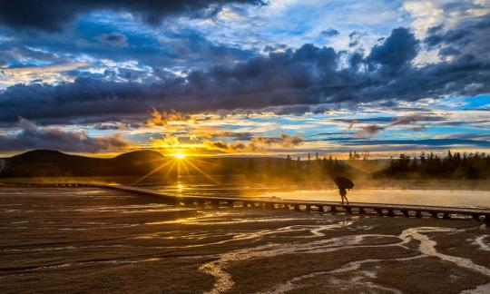 A shadowed figure walks toward a golden sunset.