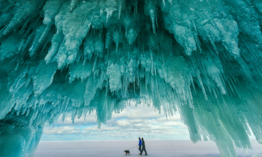 Two visitors walk by the hanging ice from the Apostle Island ice caves with its blue tinge