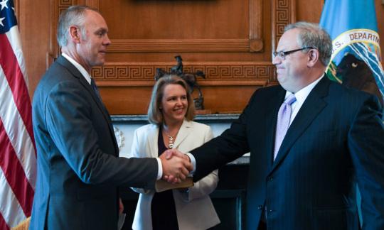 Secretary Zinke and Deputy Secretary Bernhardt wear business suits and shake hands inside a wood paneled office.