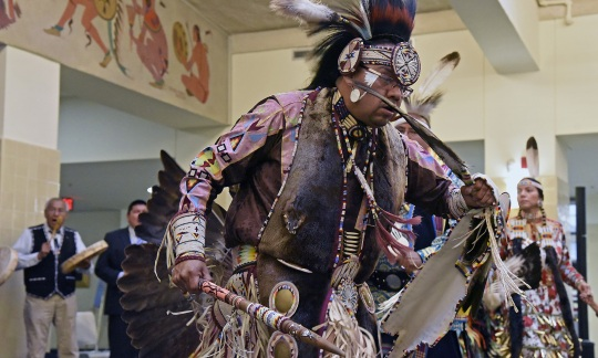 A native american man in ornate traditional clothes holds large feathers and dances with other Native Americans inside a large room.