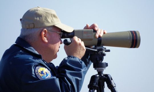 A man in a blue jacket and tan hat looks surveys wildlife on a blue sunny day by looking through a telescope.