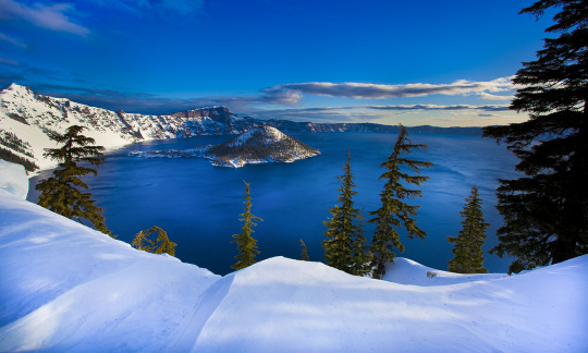 Snow covered cliffs with scattered green trees slope down to a blue lake.