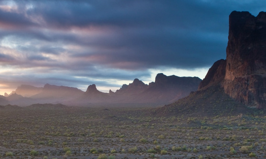 The Eagle Tail Mountains jut up over a flat desert as the sky darkens in the background.