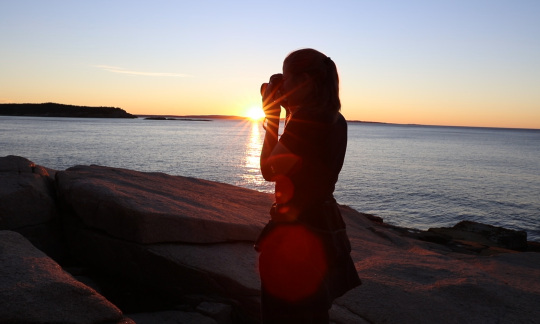 A woman's silhouette against a sun setting over the water.