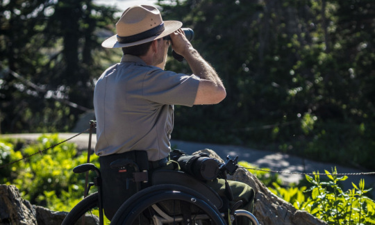A caucasian man in a national park service uniform and hat sits in a wheelchair and uses binoculars to look through trees towards a mountain.