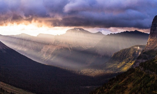 light steams through the clouds into a valley