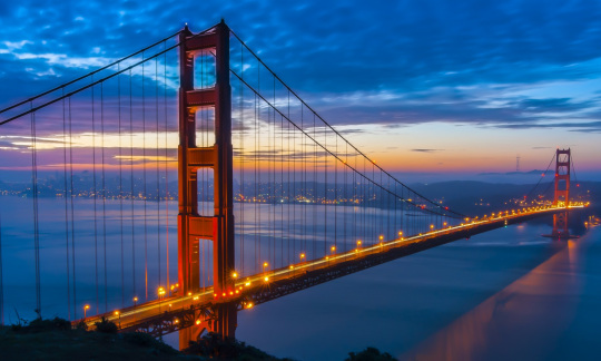 The orange Golden Gate Bridge spans a wide bay with the skyline of San Francisco at dusk in the background.