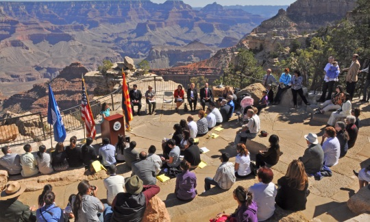 Dozens of people sit on steps and listen to a speaker behind a podium with the Grand Canyon stretching out in the background.