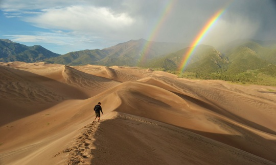 man walks across sand dunes with a double rainbow in the distance