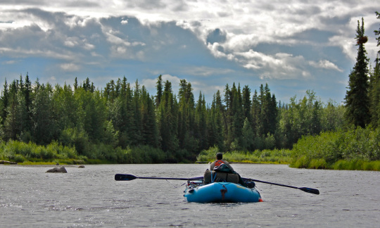 A person paddles a blue rubber boat down a calm, wide river past tall green trees under a cloudy, blue sky.