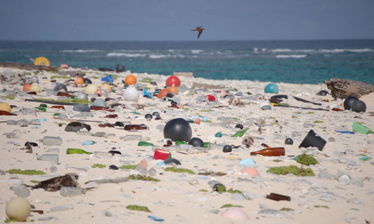 A white sand beach is littered with a large amount of colorful and clear plastic trash like balls and bottles.