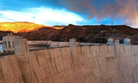 The massive sloping concrete wall of Hoover Dam stands between the red rock walls of a canyon, holding back a large lake of water with a rainbow in the sky above it.