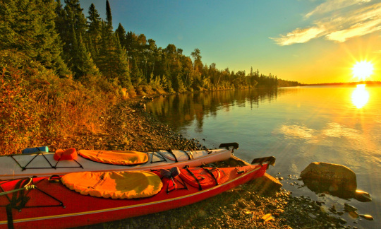 Two kayaks sit on the rocky shore. A bright sunset shines over the blue water, and a forest lines the shore's edge.