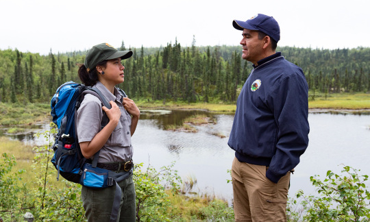 Deputy Secretary Mike Connor talks with a young female park ranger in front of a lake.