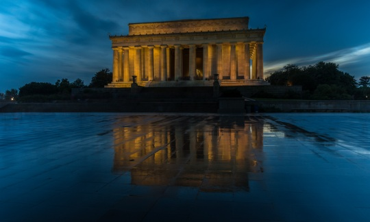 The long rectangular Lincoln Memorial is lined with columns and lit with yellow lights against a dark blue sky.