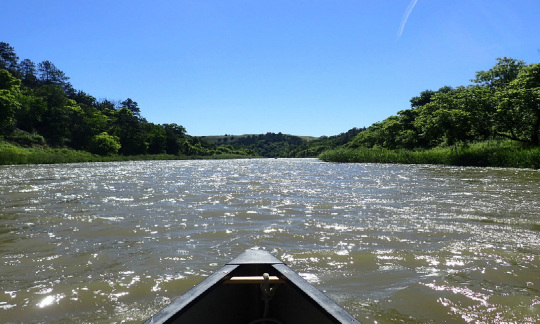 A canoe floats down the Niobrara River on a day with clear blue skies.