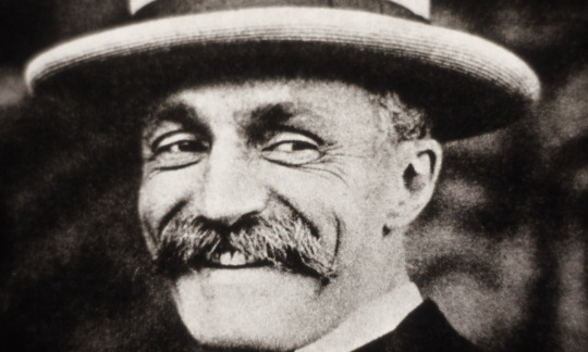 A black and white photo shows Gifford Pinchot smiling with his hat and bushy moustache.