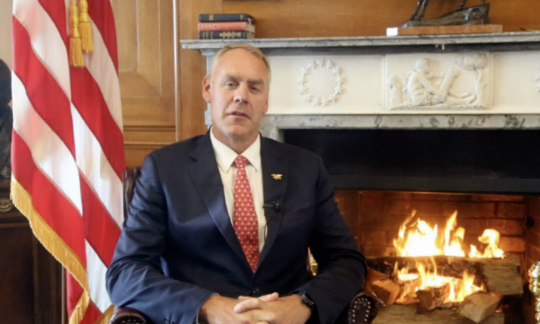 Secretary Zinke wears a suit and sits in a chair in an office with a fireplace and an American flag behind him.