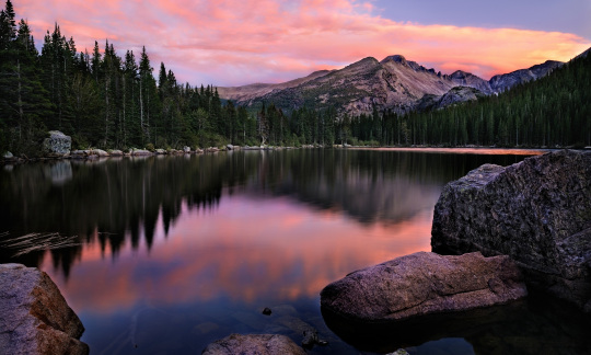 A mountain peak reflected in a lake as the sunsets, turning the sky pink