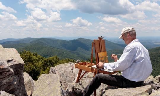 An artist sits on rocks with his easel and paints the rolling green hills of Shenandoah.