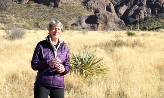Secretary Jewell stands in a grassy field with boulders and hills behind her.