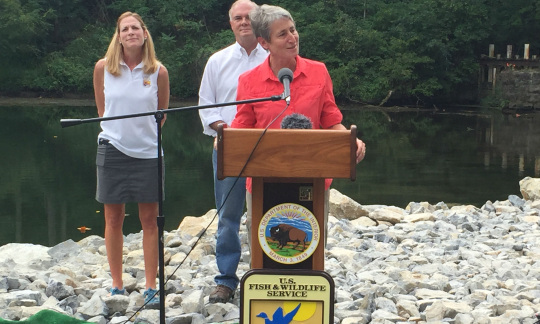 Secretary Jewell speaking at a podium with a river behind her.