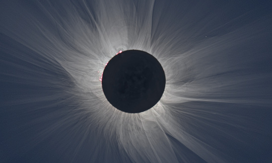 The black circle of the moon blocks the sun with light streaming around its edges.