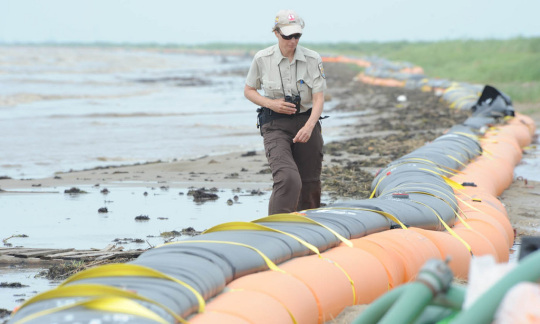 A U.S. Fish and Wildlife Service employee walks by large inflatable barricades along a beach covered with oil.
