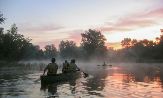 Canoers paddle through river at sunset.