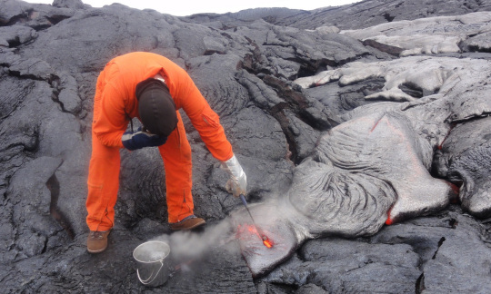 A scientist in orange protective gear dips a tool into red hot lava, extracting it from surrounding grey rock from a volcano.