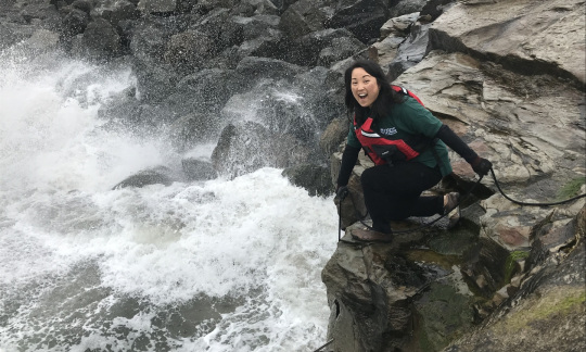An Asian American woman in a green USGS shirt and safety gear kneels on a large rock and lowers a metal scientific instrument into the white water of a river below her.