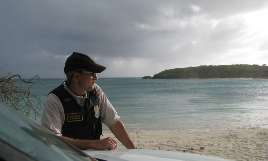 A man wearing the uniform of a U.S. Fish and Wildlife Service officer stands on a beach with a storm over the ocean behind him.
