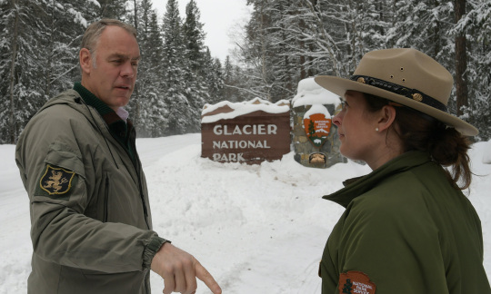 Secretary Zinke talks to a female ranger in front of the sign for Glacier National Park.